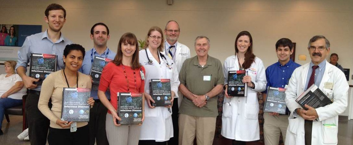 "UVA emeritus professor Gerry Mandell (center, with ID chief Bill Petri) presents 2014-2015 ID fellows with copies of his textbook ""Principles and Practices of Infectious Diseases."""